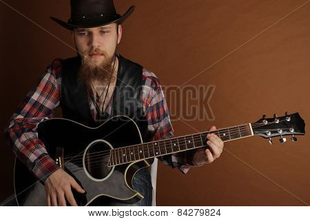 portrait of the young man with a beard and a guitar