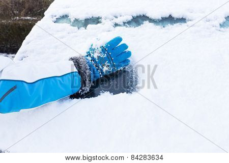Arm with glove removing snow from car window