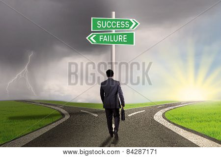 Entrepreneur With Signpost To Success Or Failure