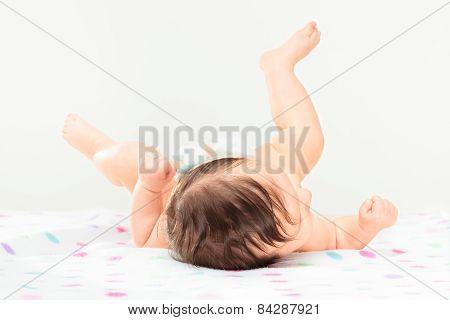 Back View Of Little Baby Girl Lying On Polka Dots Blanket