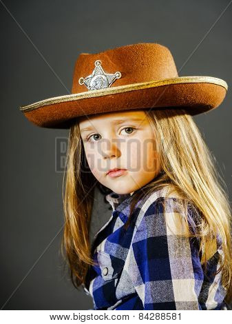 Cute Little Girl Dressed In Cowboy Shirt And Sheriff Hat