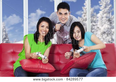 Group Of Friends Playing Games On Sofa