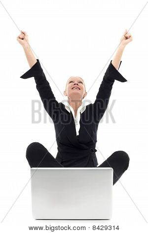 portrait of a young caucasian businesswoman sitting on the floor with arms up and laptop