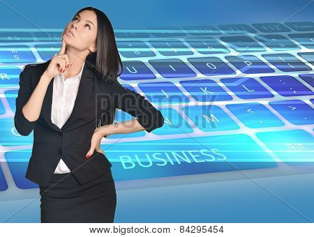 Business woman looking up forefinger pressed chin stands on keyboard background
