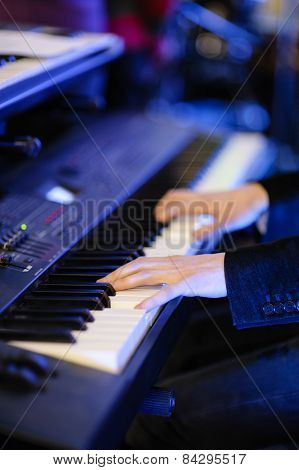 hands of musician playing keyboard