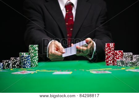 Respectable casino worker in a tuxedo with a red tie serving cards