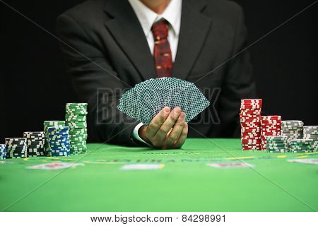 Respectable casino worker in a tuxedo with a red tie shuffling cards