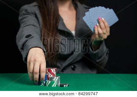 Blackjack in a casino, a woman makes a bet, and puts a chip
