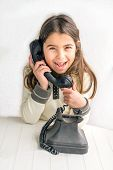 foto of 7-year-old  - Seven year old girl with old vintage phone before white background - JPG