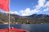 stock photo of annecy  - Annecy Lake and mountains from boat and red flag