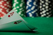 stock photo of poker hand  - two poker cards aces with poker chips in the background - JPG