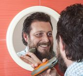 picture of beard  - Bearded man trim his beard with electric shaver - JPG