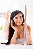 stock photo of toothless smile  - Beautiful young smiling woman adjusting her headphones while listening to the MP3 player in bed - JPG