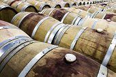 stock photo of wine cellar  - A red wine barrel room at a vineyard in which there are barrels as far as the eye can see - JPG