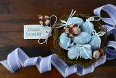 foto of bird egg  - Happy Easter blue decoration eggs in birds nest on dark wood table background - JPG