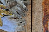stock photo of dirty  - Old safety gloves on wooden background - JPG
