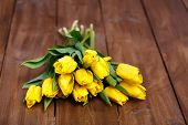 stock photo of yellow buds  - Big bouquet of beautiful yellow flowers, tulips, lie on the wooden floor of the old brown boards, green stems and leaves, dense buds of yellow tulips, recently cut in the flowerbed.