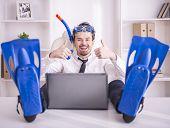 stock photo of fin  - Happy businessman is working in office is wearing in fins - JPG