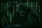 picture of computer hacker  - Hacker looking for password and user information using digital tablet and laptop computer - JPG