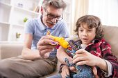 foto of grandpa  - Toddler boy and his grandpa are playing with a plane toy. ** Note: Shallow depth of field - JPG