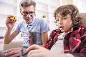 stock photo of grandpa  - A preschooler and his grandpa happily are playing with toy dinosaurs.