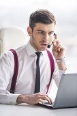pic of query  - Businessman is taking a call on a headset as he deals with queries at the customer support call centre - JPG