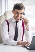 picture of query  - Smiling businessman is taking a call on a headset as he deals with queries at the customer support call centre - JPG