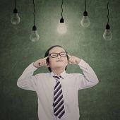picture of business class  - Pensive business kid under lit bulbs with eyes closed in class - JPG