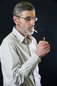 image of cigarette lighter  - Middle aged man lighting a cigarette - JPG