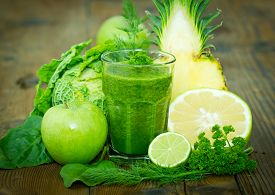 stock photo of smoothies  - Healthy green smoothie with fresh vegetables and fruits on the table - JPG