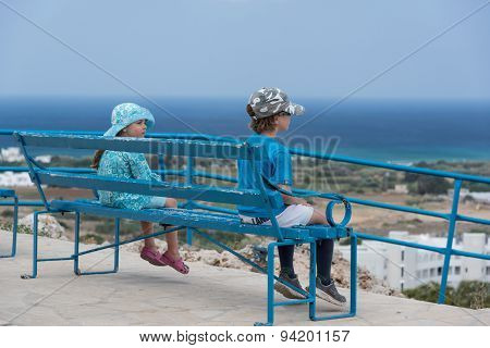 Small Boy And Girl Sitting On A Blue Bench And Looking Down The Hill On The Sea