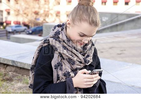 Teenage Girl With Cell Phone Outdoors.