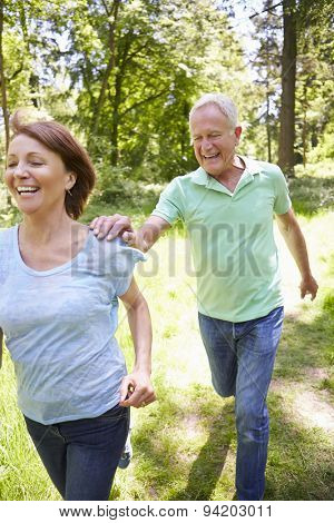 Senior Couple Running In Summer Countryside