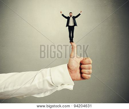 happy small businessman standing on big thumbs up and raising his hands up over dark grey background