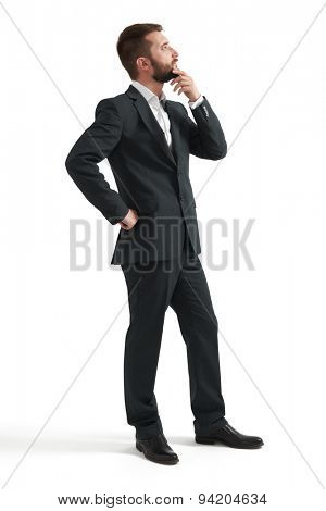 serious thoughtful businessman in formal wear holding his hand at chin and looking up. isolated on white background