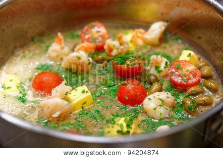Shrimps being cooked in broth and butter with tomatoes, capers and parsley