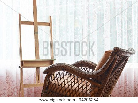 Wicker rocking chair and wooden easel composition