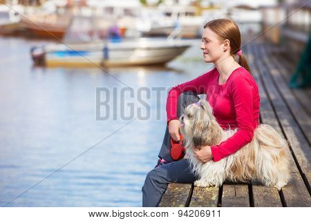 Young woman with shih-tzu dog sitting on town quay with boats.