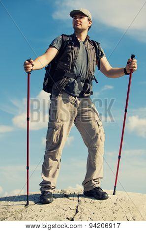Young man tourist with backpack and sticks standing on mountain top.