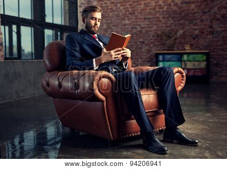 Young handsome businessman with beard in black suit sitting on chair reading book. Focus on face.