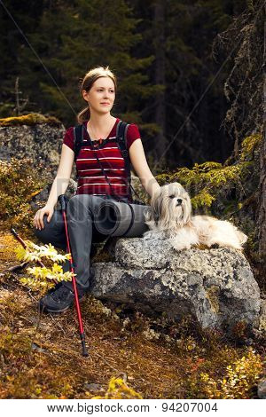 Young woman tourist sitting on stone with dog in autumn forest.