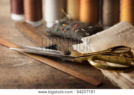 Sewing textile or cloth. Gold scissors pin cushion, and natural white fabric. Work table of a tailor. Shallow depth of field, Focus on scissors