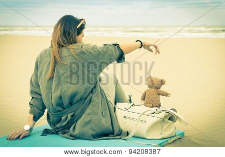 Young Single Woman Sitting At The Beach With Her Teddy Bear Looking At The Sea - Vintage Retro