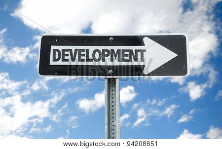 Development direction sign with sky background