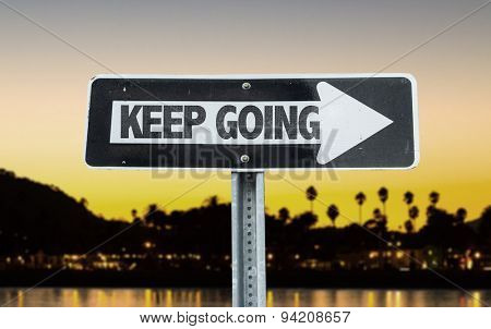 Keep Going direction sign with sunset background