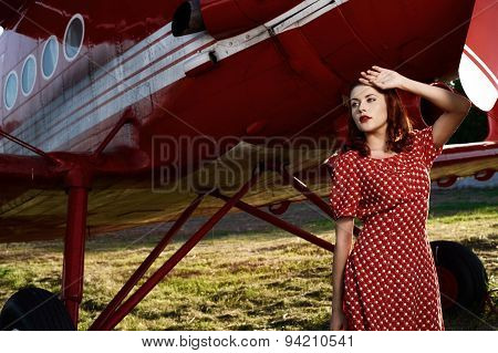 pin-up female stands against airplane in red dress