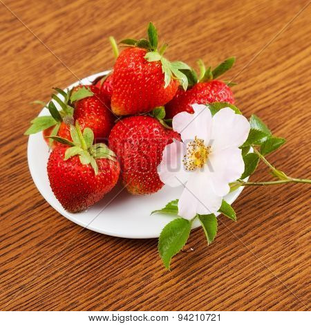 several strawberries on a plate on a table with a flower. close-up