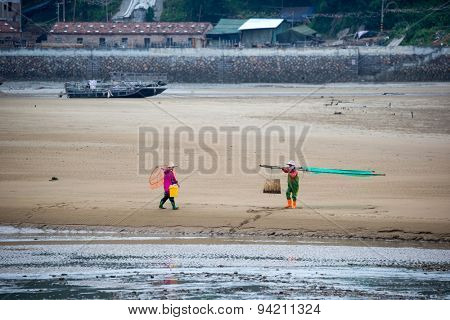 XIAPU, CHINA - JUNE 4, 2015: Fishermen walking out to sea to harvest crabs from the crab farms offshore. Xiapu is a major fishermen's port and has an important seafood farming industry in China.