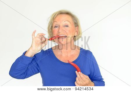 Senior Woman Biting A Red Hot Chili Pepper