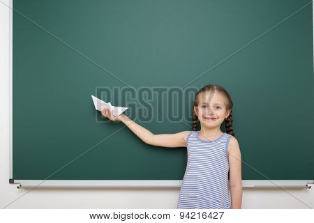 Schoolgirl with paper toy ship near school board